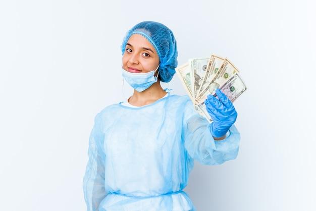Junge mischrassen-doktorfrau, die dollar lokalisiert auf weißem hintergrund hält