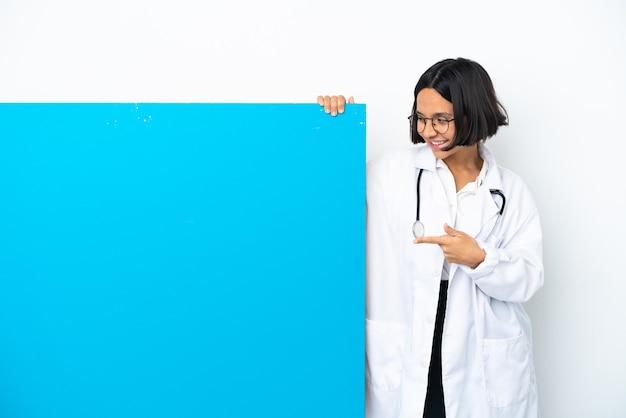Junge mischrassen-doktorfrau mit einem großen plakat lokalisiert auf weißem hintergrund, der finger zur seite zeigt und ein produkt präsentiert