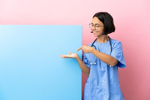 Junge mischrassenchirurgin mit einem großen banner über lokalisiertem hintergrund, der imaginären copyspace auf der handfläche hält, um eine anzeige einzufügen