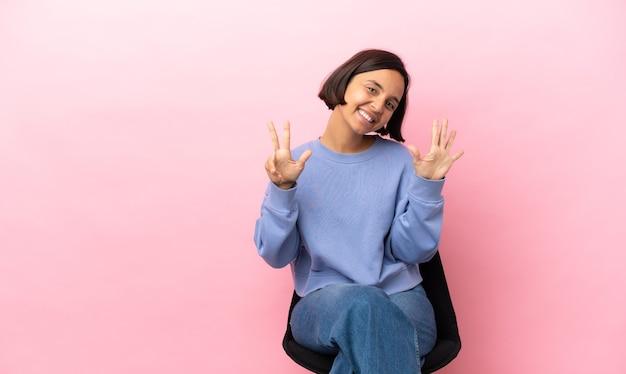 Junge mischrassenfrau, die auf einem stuhl lokalisiert auf rosa hintergrund sitzt und acht mit den fingern zählt