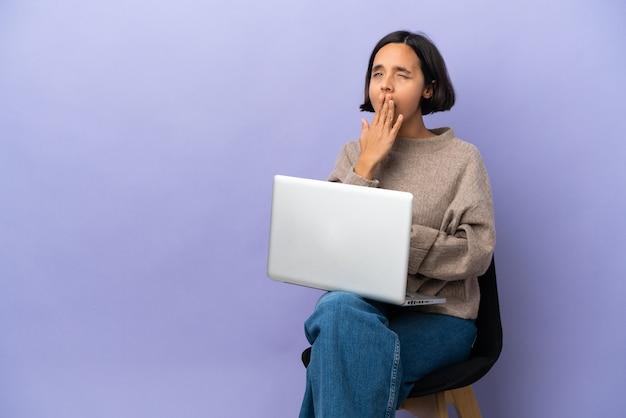 Junge mischrassenfrau, die auf einem stuhl mit laptop lokalisiert auf lila hintergrund gähnt und weit geöffneten mund mit hand bedeckt