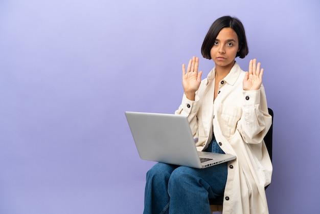 Junge mischrassenfrau, die auf einem stuhl mit laptop lokalisiert auf lila hintergrund sitzt, der stoppgeste macht und enttäuscht