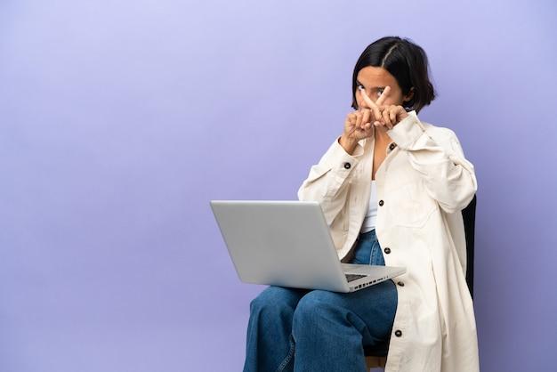 Junge mischrassenfrau, die auf einem stuhl mit laptop lokalisiert auf purpurrotem hintergrund sitzt und stoppgeste mit ihrer hand macht, um eine handlung zu stoppen