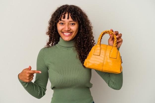 Junge mischrassenfrau, die eine handtasche lokalisiert auf weißer wandperson hält, die von hand auf einen hemdkopierraum zeigt, stolz und zuversichtlich