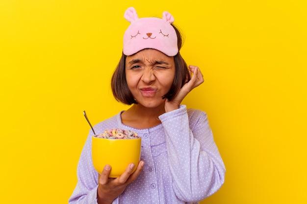 Junge mischrassenfrau, die müsli isst, die einen pijama tragen, der auf gelben wandabdeckungsohren mit händen isoliert wird.