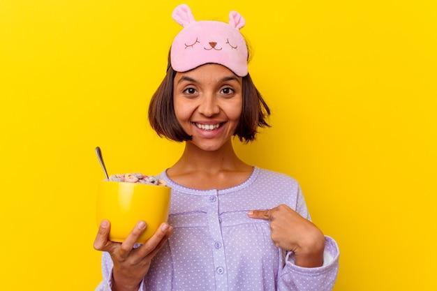 Junge mischrassenfrau, die müsli isst, die einen pijama tragen, der auf gelber hintergrundperson lokalisiert wird, die von hand auf einen hemdkopierraum zeigt, stolz und zuversichtlich