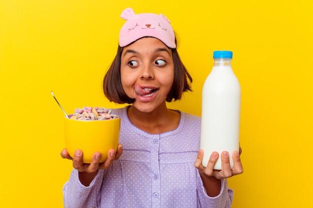 Junge mischrassenfrau, die müsli trägt einen pijama trägt, der auf gelbem hintergrund lokalisiert wird