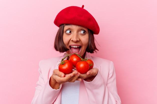 Junge mischrassenfrau, die tomaten lokalisiert auf rosa hintergrund hält