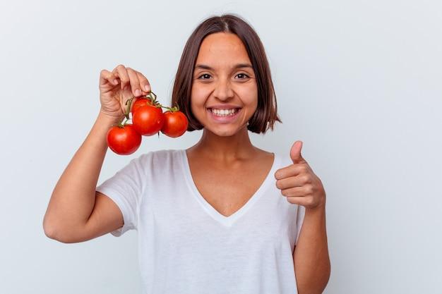 Junge mischrassenfrau, die tomaten lokalisiert auf weißem hintergrund hält