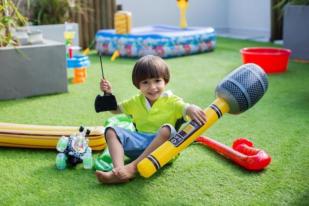 Junge mit aufblasbarem mikrofon. aufblasbares spielzeug für den sommer
