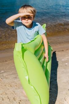 Junge mit aufblasbarer matratze starrte auf küste