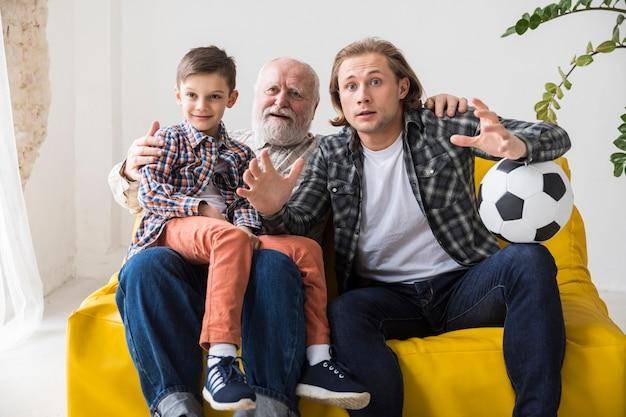 Junge mit aufpassendem fußball des vaters und des großvaters zu hause