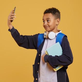 Junge mit blauem rucksack, der ein selbstfoto macht