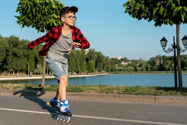Junge mit blauen rollenblättern im park