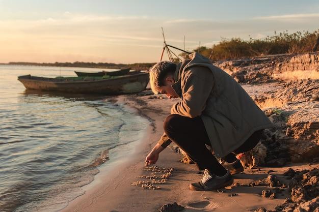Junge mit blonden haaren, die auf den sand schreiben, am meeresufer.