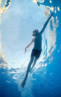Junge mit brille, der in transparentem wasser schwimmt