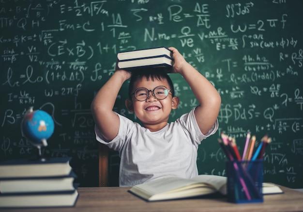 Junge mit büchern im klassenzimmer sitzen