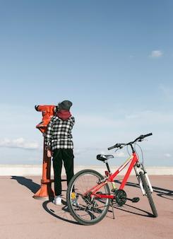 Junge mit dem fahrrad, das durch teleskop draußen schaut