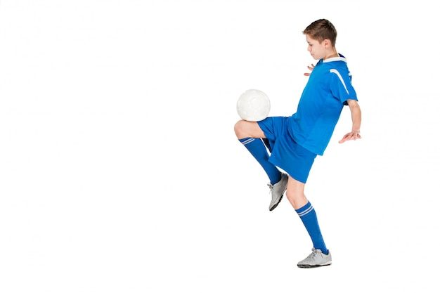 Junge mit dem fußball, der fliegenden tritt tut