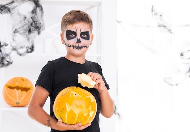 Junge mit dem gesicht gemalt, einen kürbis halten