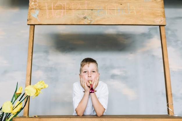 Junge mit dem parteigebläse, das geburtstag feiert
