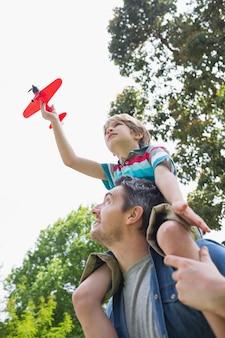 Junge mit dem spielzeugflugzeug, das auf den schultern des vaters sitzt