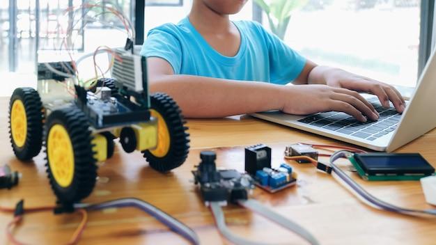 Junge mit dem tablet-pc-computer, der elektrische spielwaren programmiert und roboter errichtet.