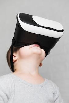 Junge mit dem virtuellen kopfhörer, der oben schaut