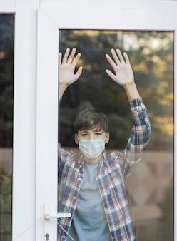 Junge mit der medizinischen maske, die draußen schaut