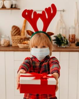 Junge mit der medizinischen maske, die ein weihnachtsgeschenk hält