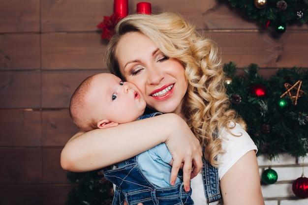 Junge mit der schönen blonden mutter, die in verziertem haus für weihnachten umfasst