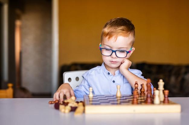 Junge mit down-syndrom mit der großen brille, die schach spielt