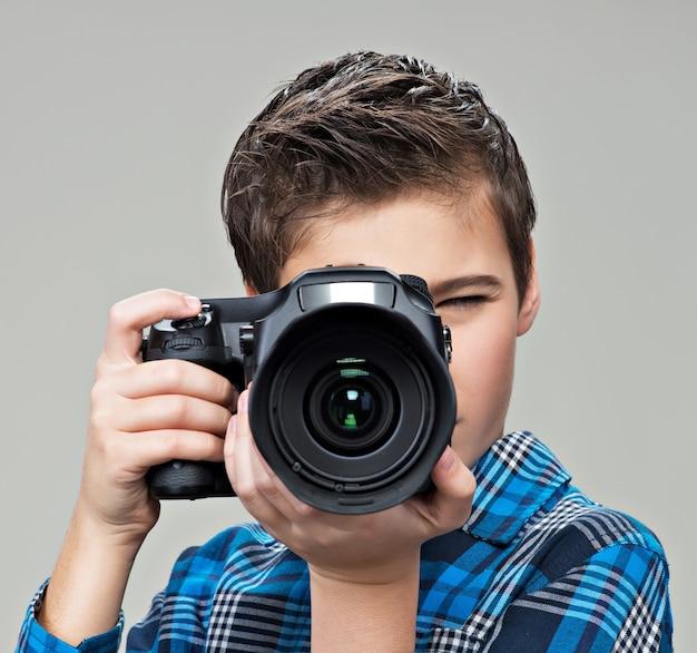 Junge mit dslr-kamera fotografiert. teen boy mit kamera beim fotografieren.
