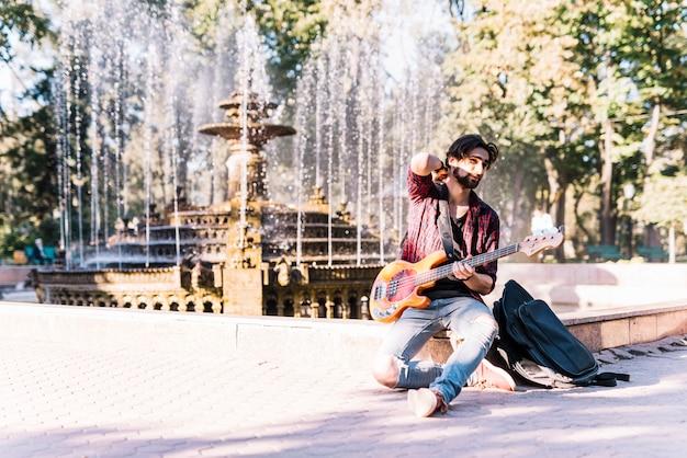 Junge mit e-gitarre am brunnen