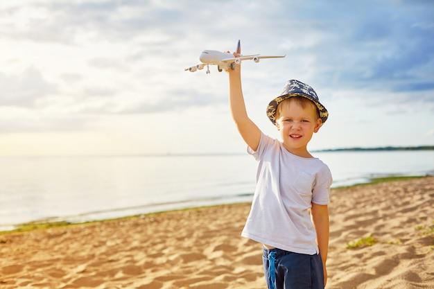 Junge mit einem flugzeug in seinen händen am strand