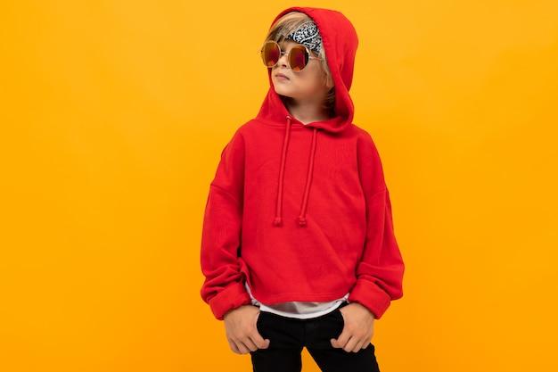 Junge mit einem kopftuch auf dem kopf in einem roten kapuzenpulli und einer brille, die auf gelb posiert