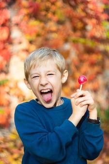 Junge mit einem lutscher in den händen zeigt lustige gesichter