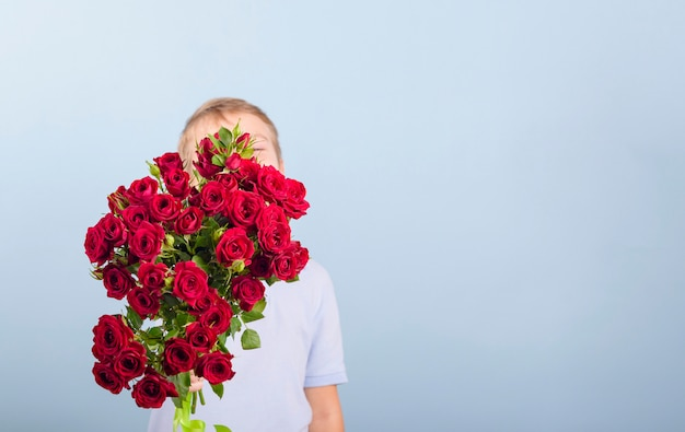 Junge mit einem strauß roter rosen als geschenk für muttertag oder valentinstag