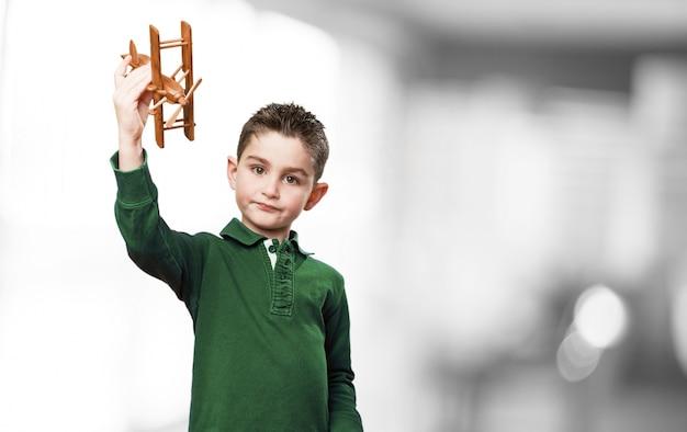 Junge mit einer holz-flugzeug spielen