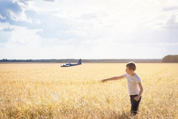 Junge mit flugzeug auf der wiese