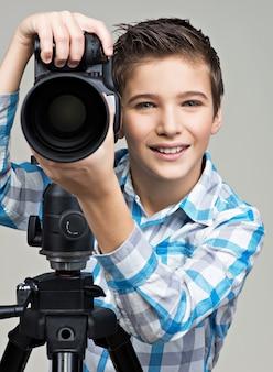 Junge mit fotokamera auf thripod, der im studio aufwirft