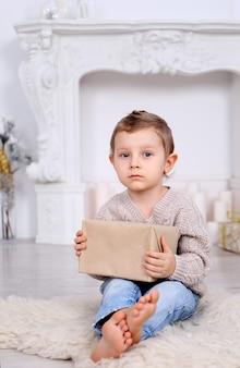 Junge mit geschenken nahe dem kamin