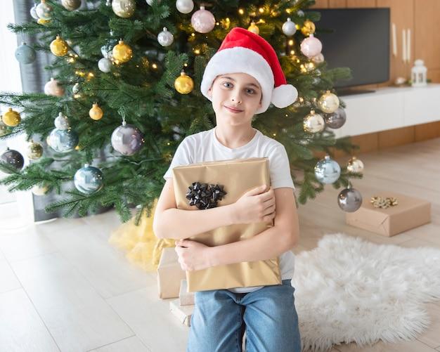 Junge mit geschenken spielt nahe dem weihnachtsbaum. wohnzimmerinnenraum mit weihnachtsbaum und dekorationen. neujahr. geschenk geben.