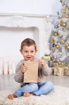 Junge mit geschenken unter dem weihnachtsbaum
