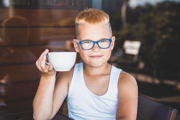 Junge mit gläsern in einem restaurant, das kaffee trinkt