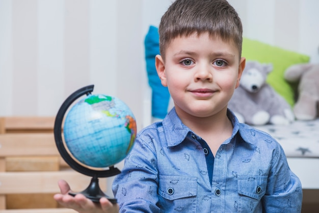 Junge mit globus in der hand