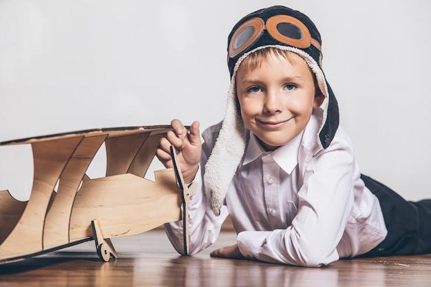 Junge mit hölzernem flugzeugmodell und einer kappe mit kappe