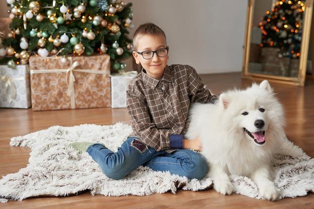 Junge mit hund in der nähe von weihnachtsbaum zu weihnachten
