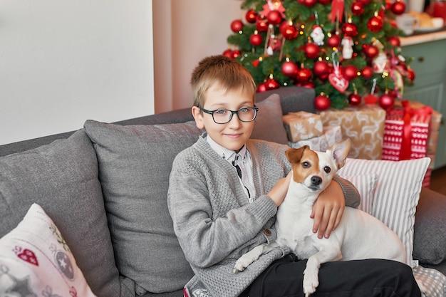 Junge mit hund nahe weihnachtsbaum auf weihnachten