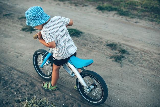 Junge mit hut, der das fahrrad auf einer landstraße reitet